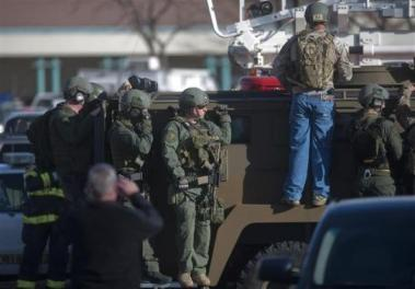 Armed law enforcement officers gather outside Arapahoe High School, after a student opened fire in the school in Centennial, Colorado